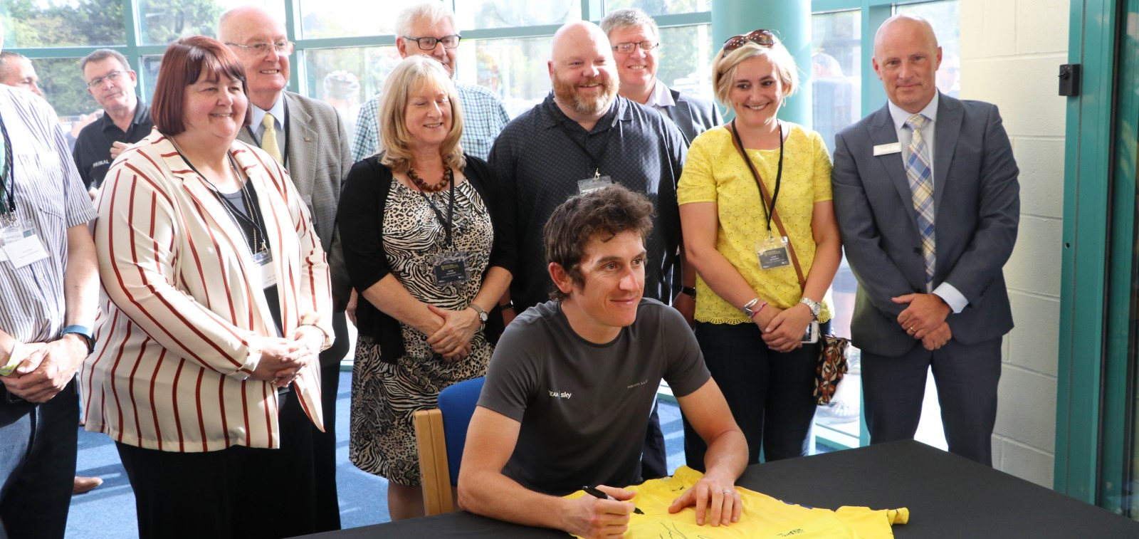 Cyclist Geraint Thomas sat a table with a line of people behind him