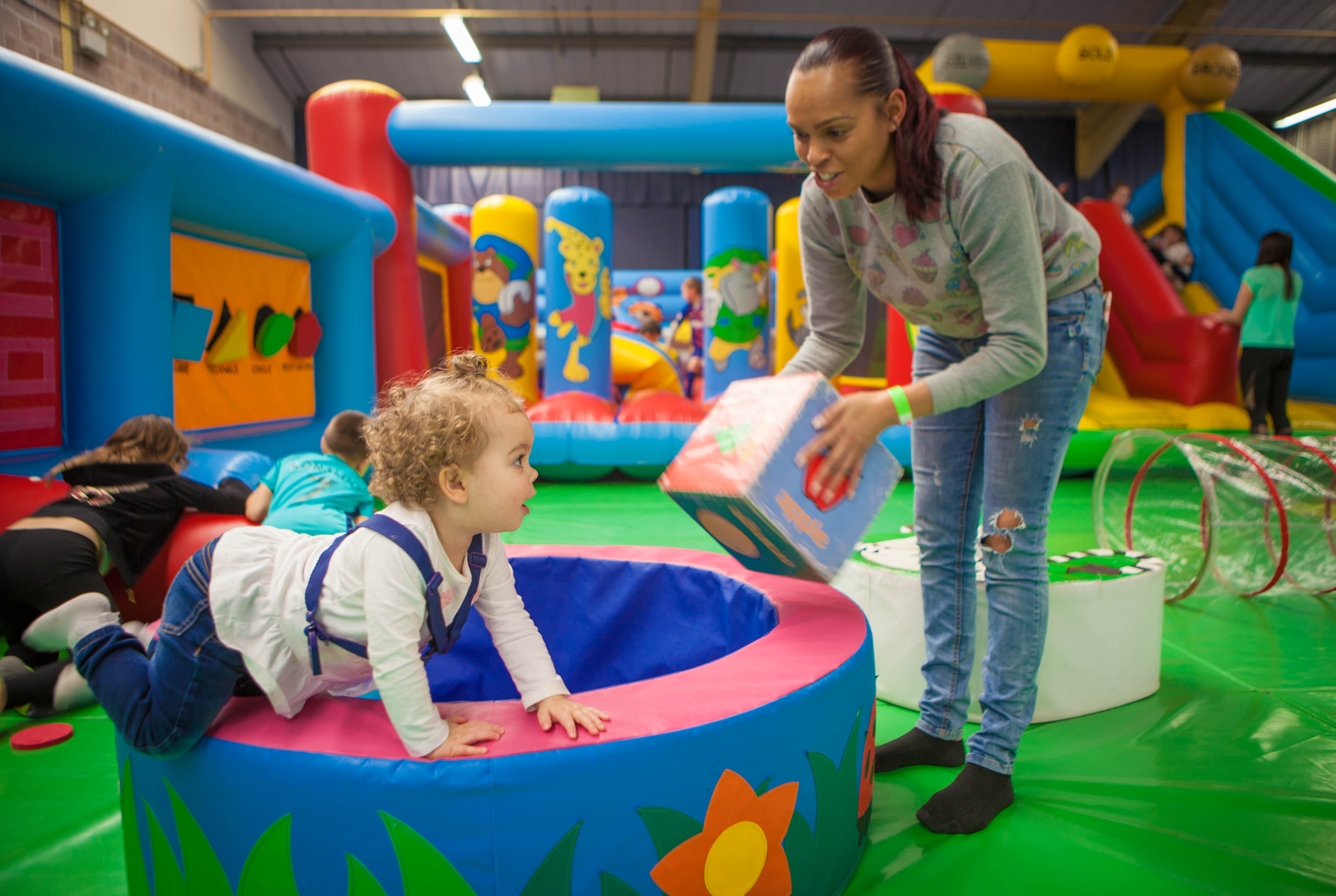 Young child climbing on softplay equipment as parent watches on