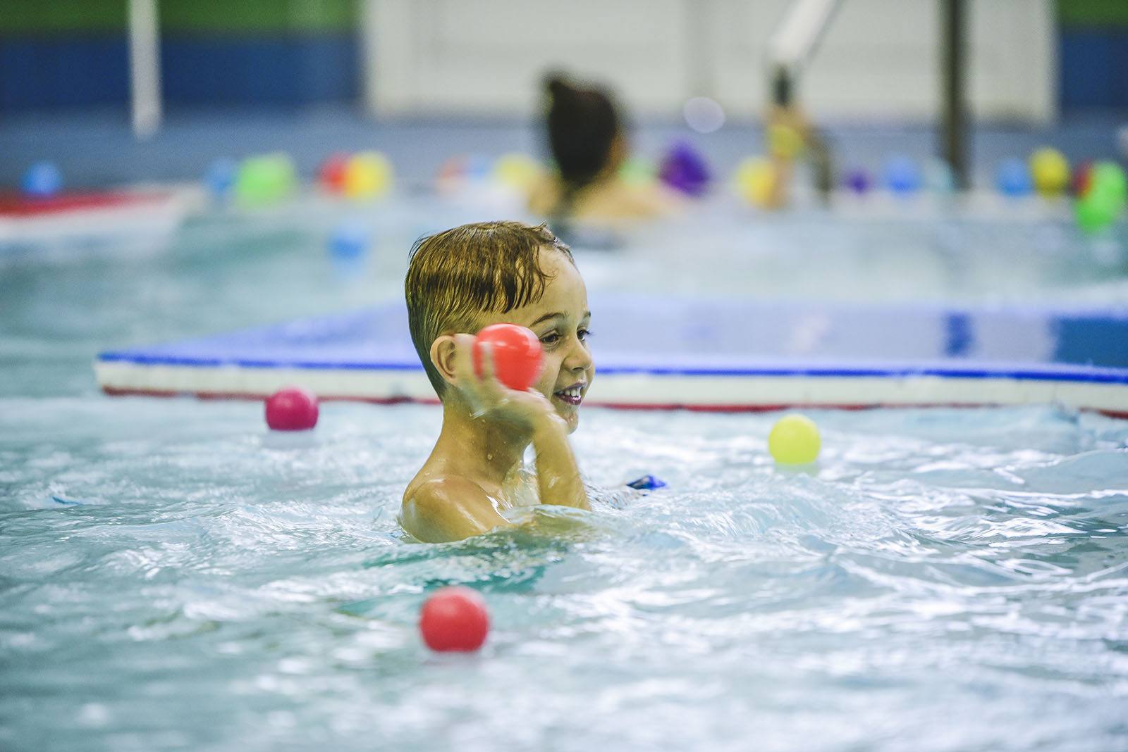 young boy playing in a swimming pool with water float balls