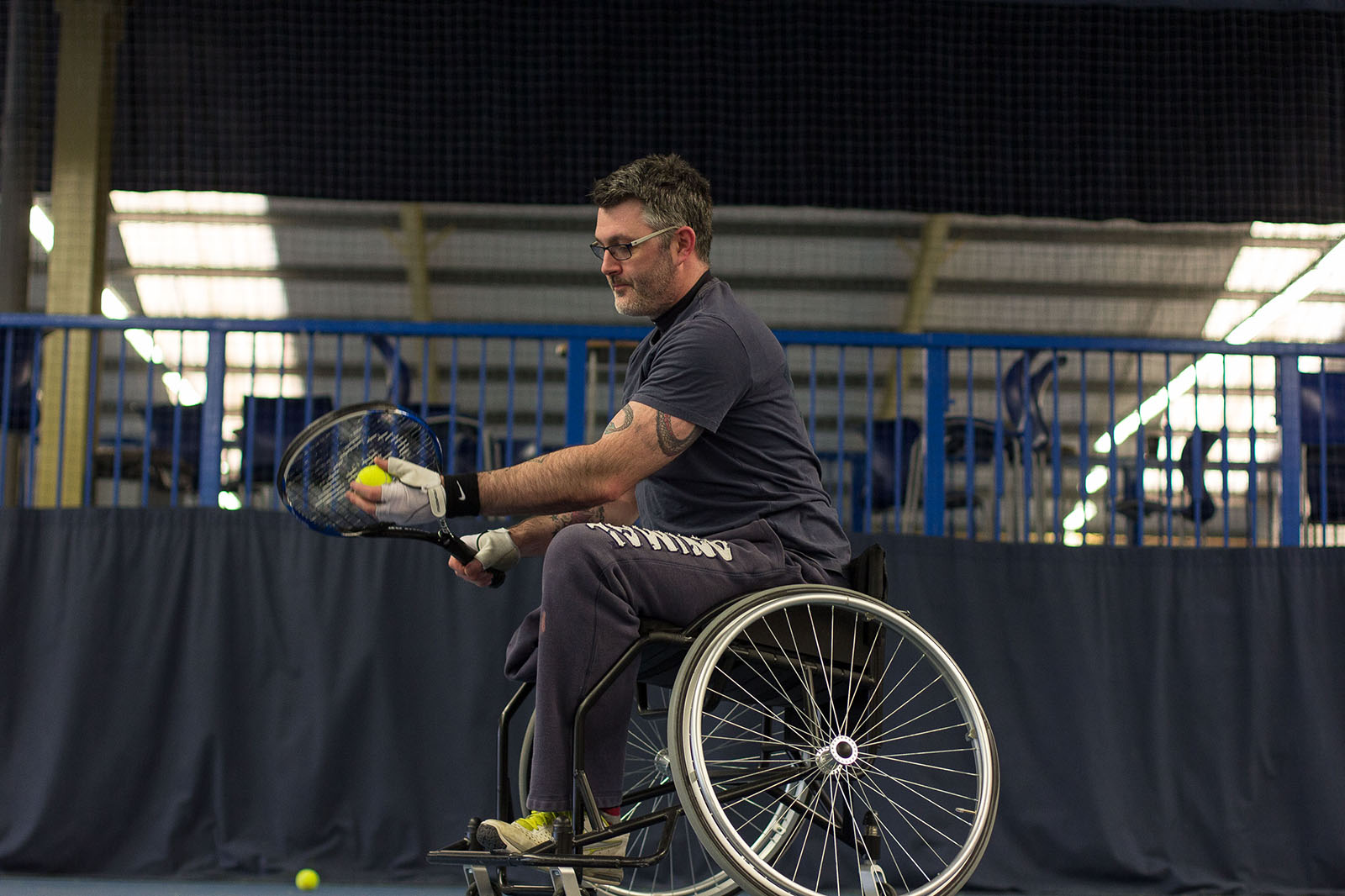 man in a wheelchair serving a tennis ball