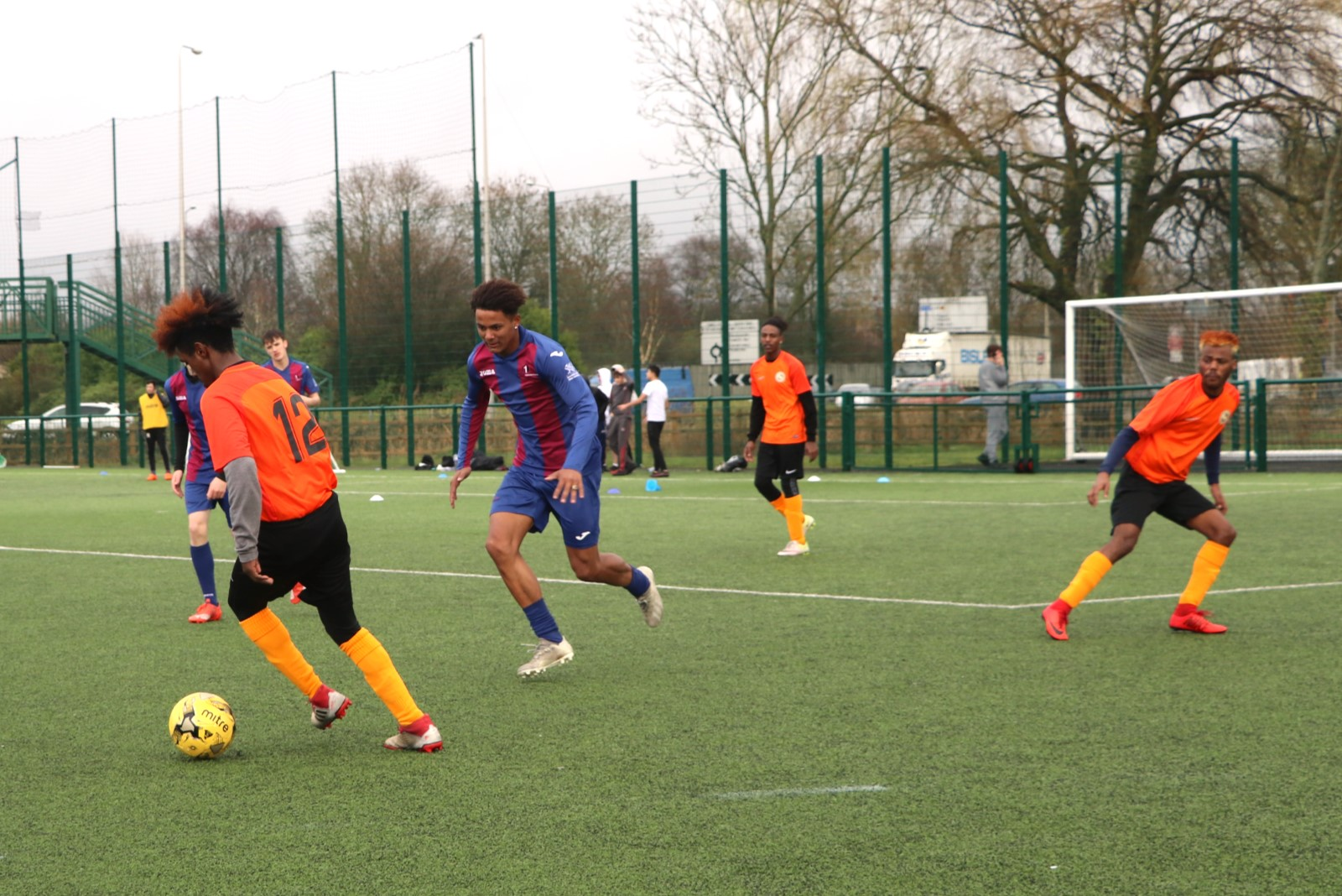 Men in orange football kit playing football.jpg