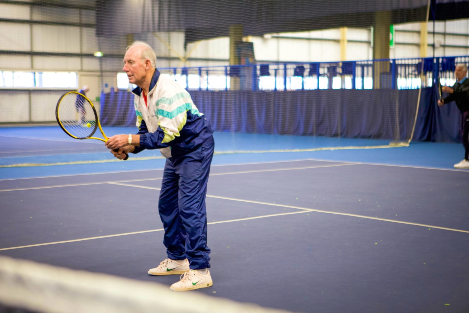 man in tracksuit holding tennis racket.jpg