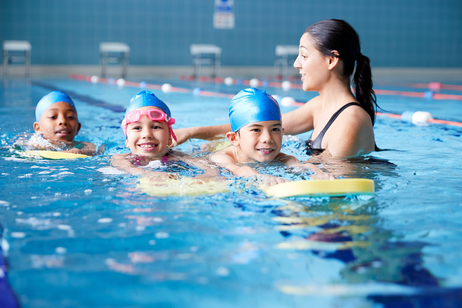 swimming instructor teaching young children how to swim with floats