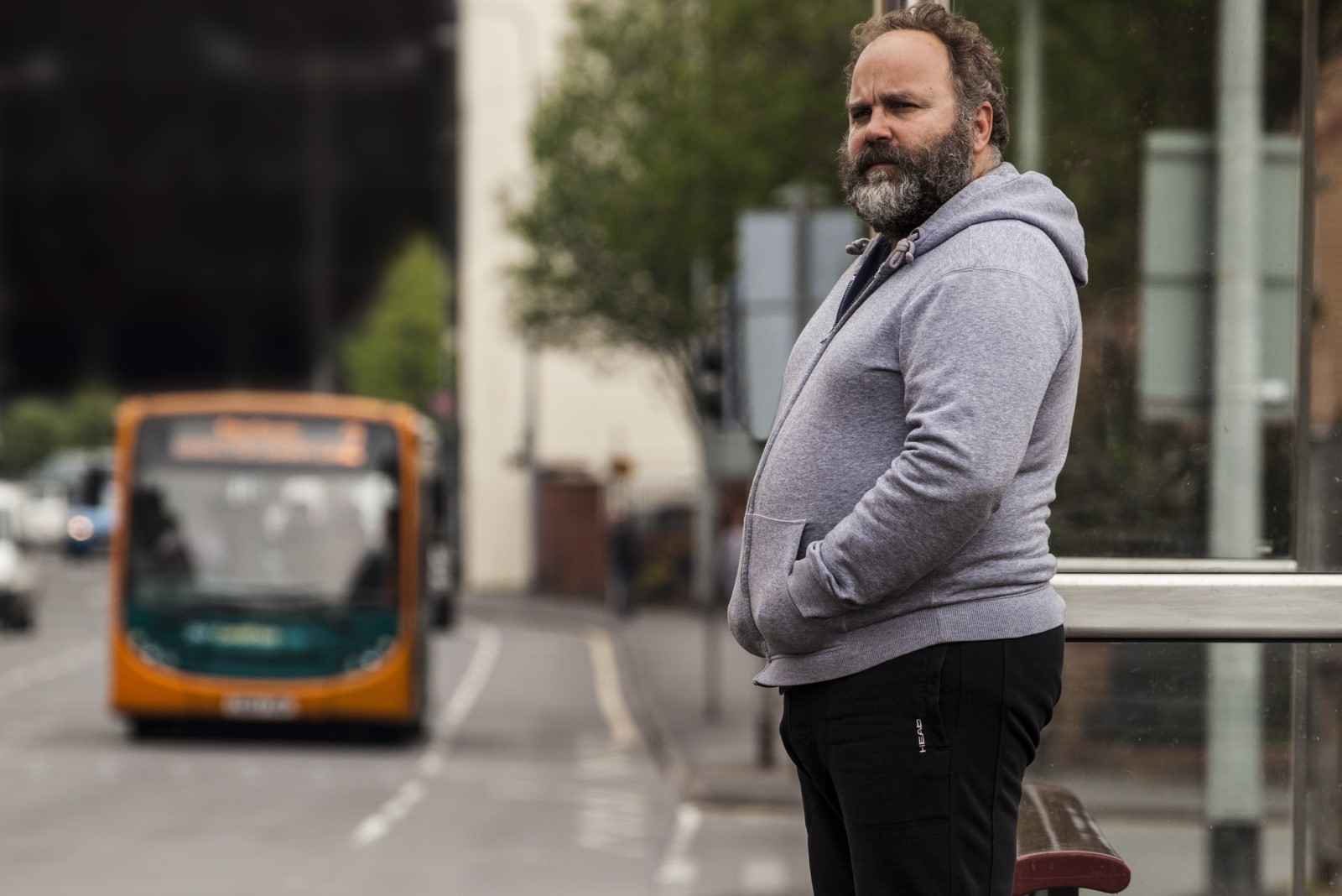 Man stood at a bus stop in a grey hoodie.jpg