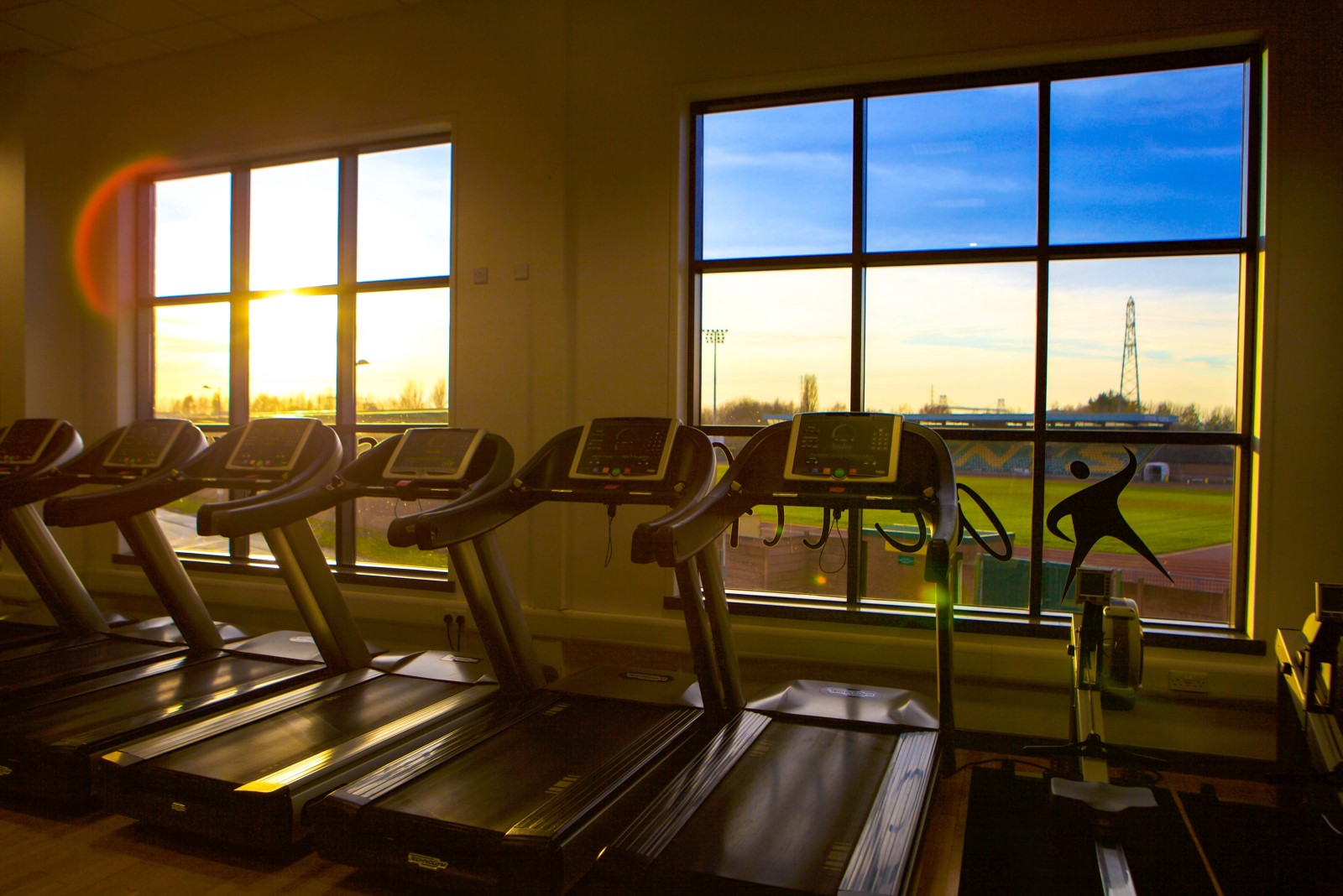 Line of tradmills with sun setting through gym window.jpg