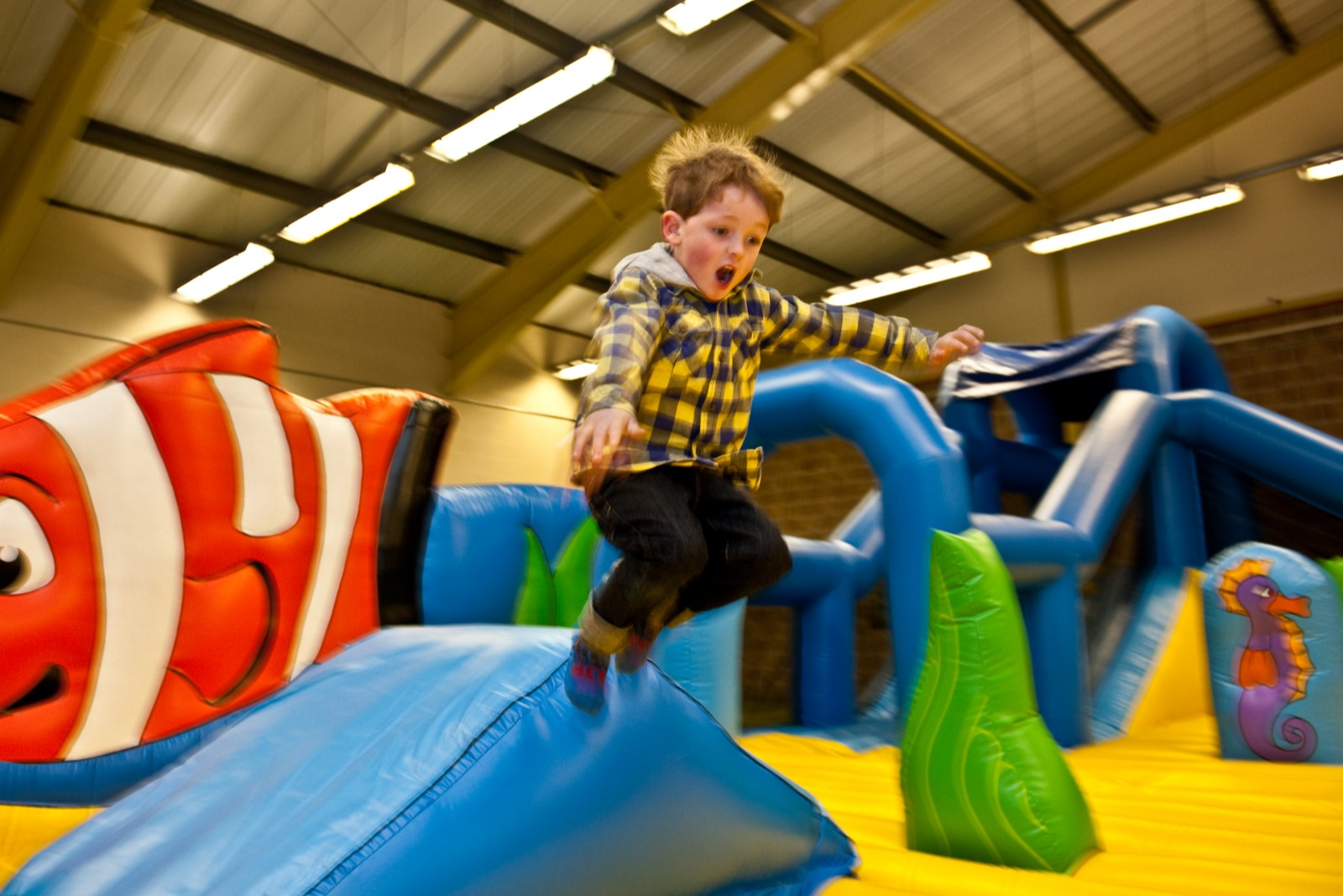 boy in yellow shirt jumping on soft play.jpg