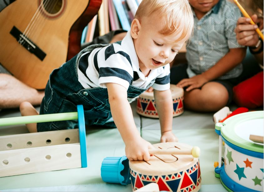 Toddler in striped tshirt playing with toy drum