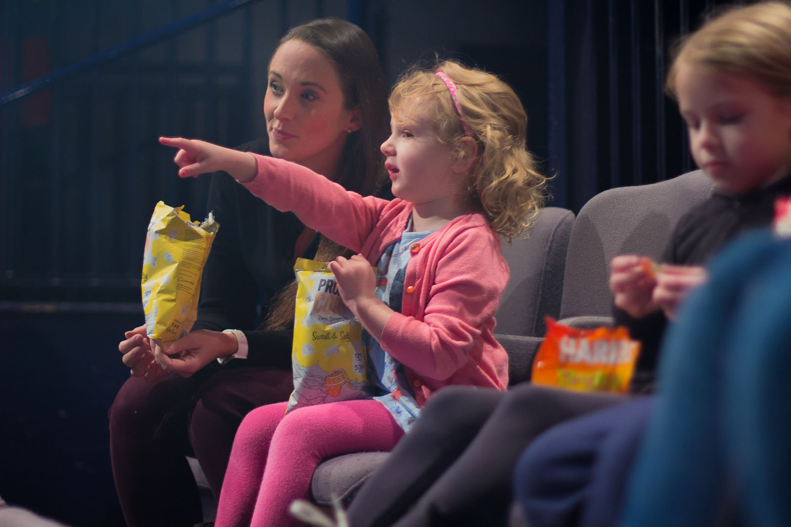 young girl pointing at a cinema screen holding popcorn