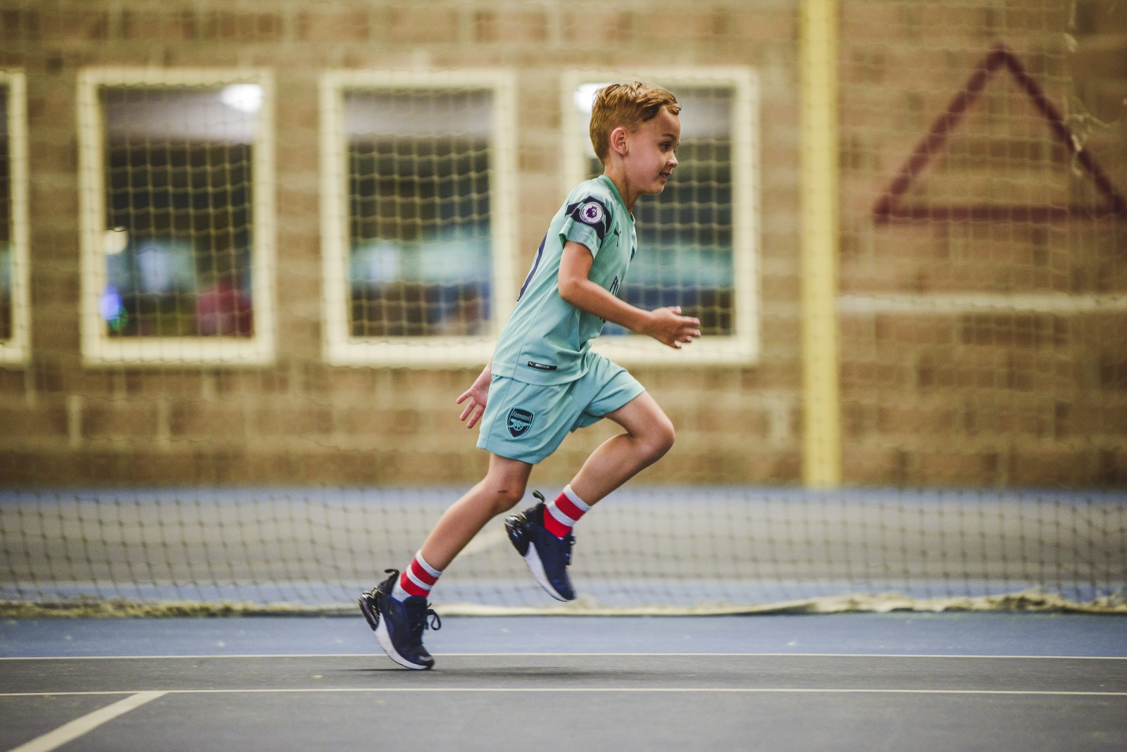 boy in a football kit running in a sports hall.jpg