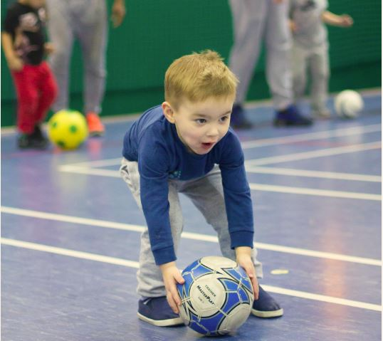 Little boy in blue top picking up a football