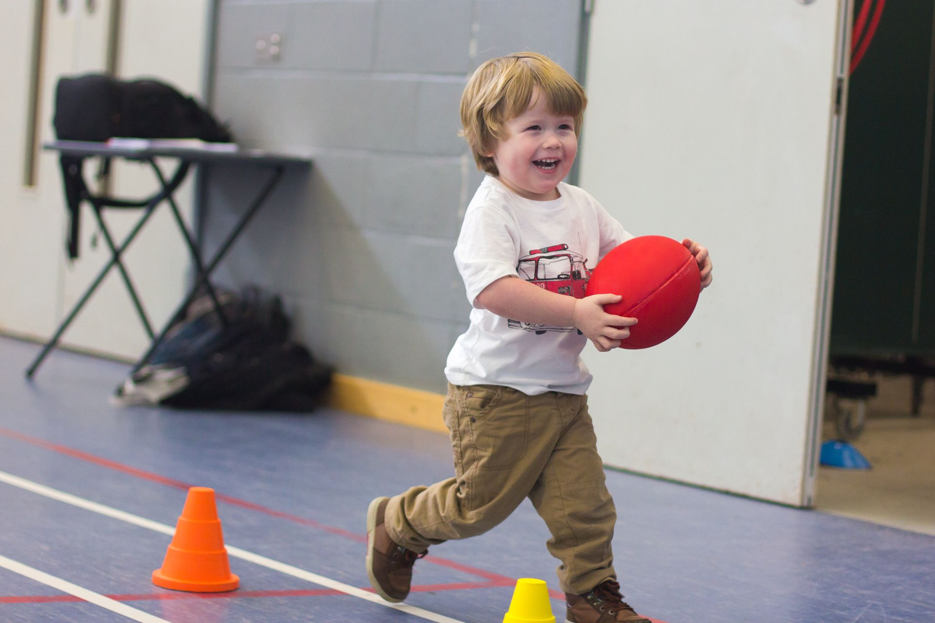 young boy running with red rubgy ball