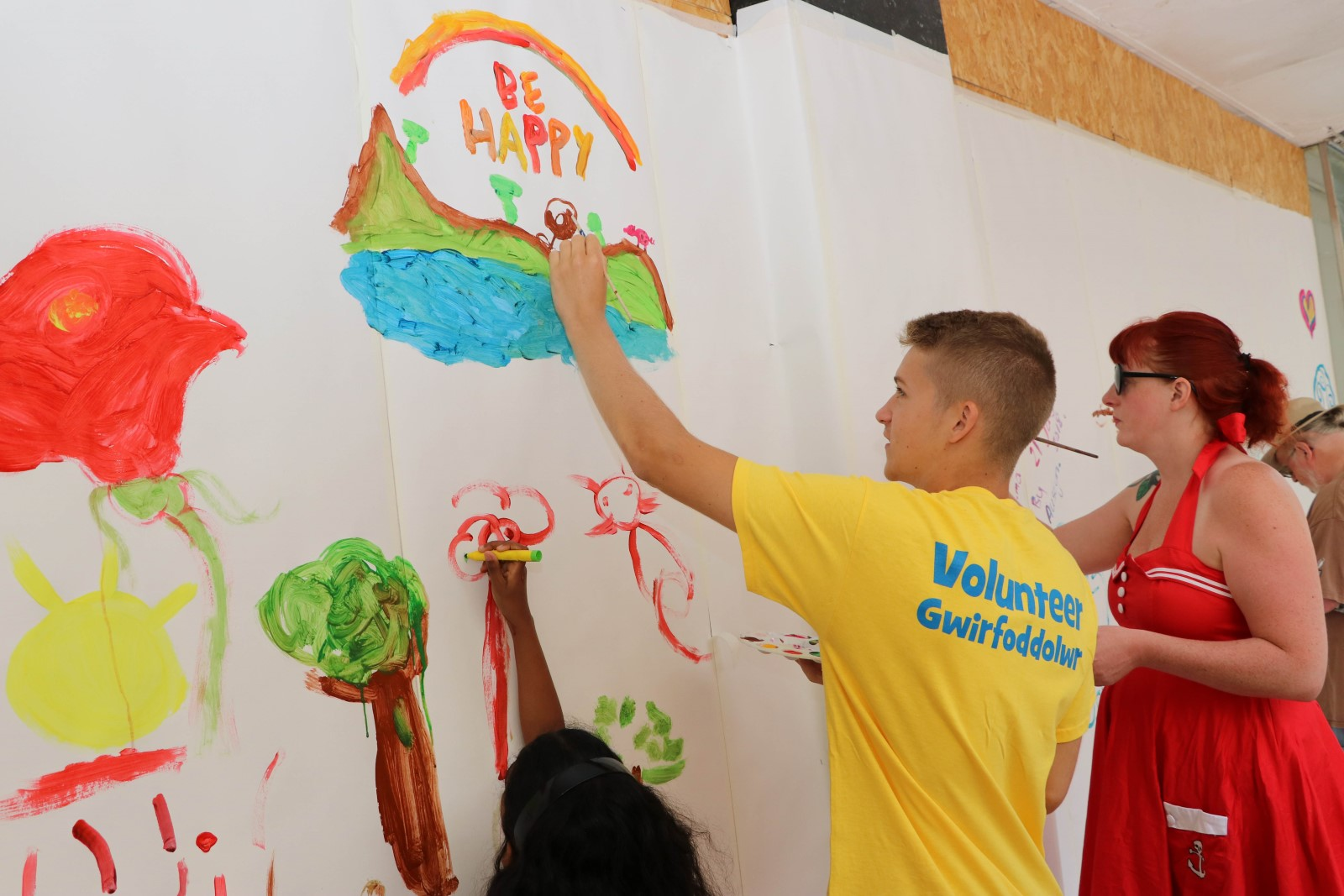 Man in volunteer t-shirt painting pictures on a wall.jpg