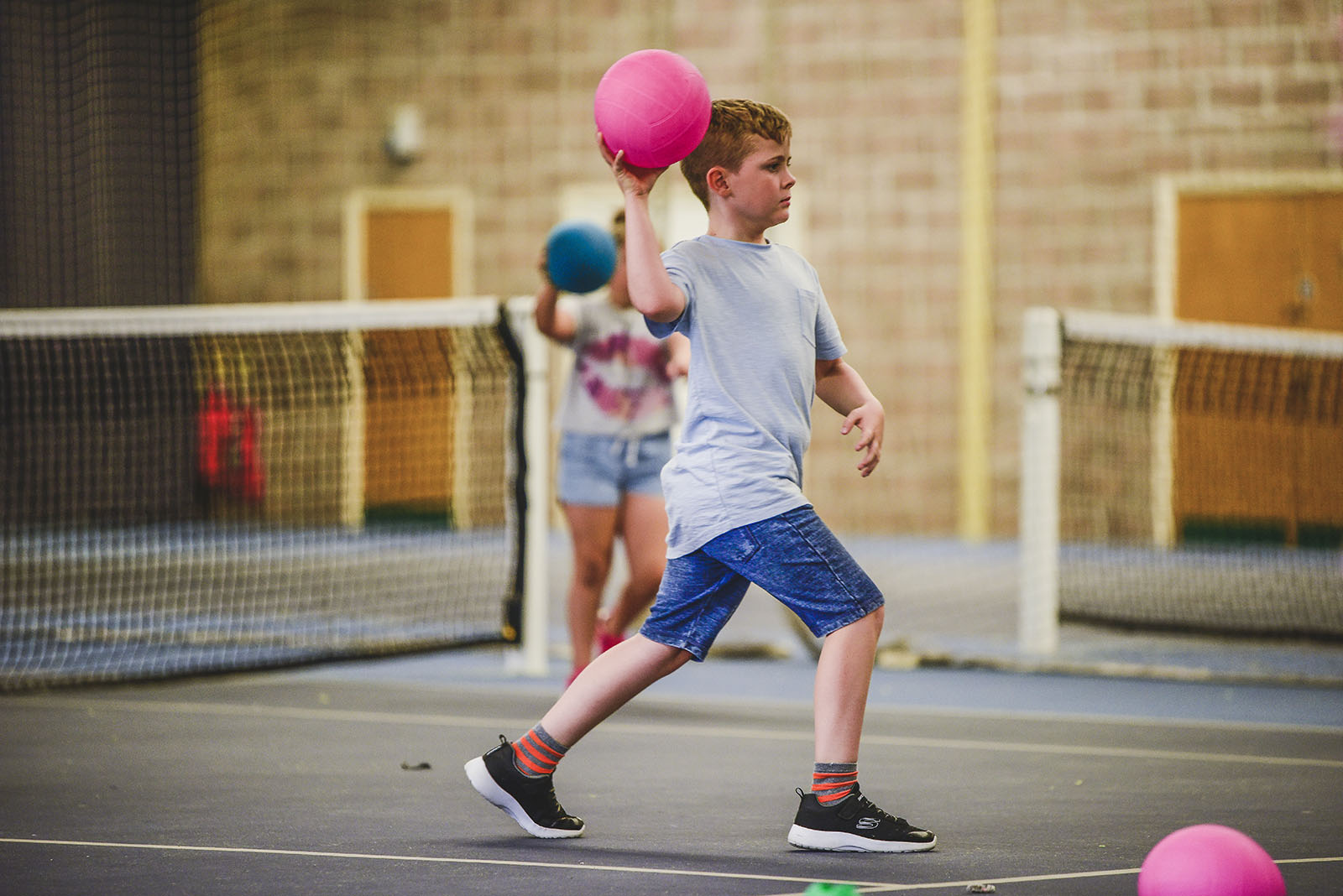 a young boy throwing a dodgeball
