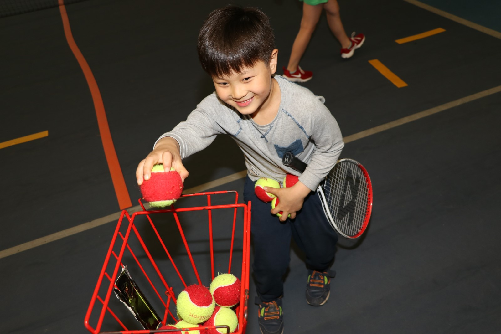 infant boy putting tennis balls in a basket.jpg