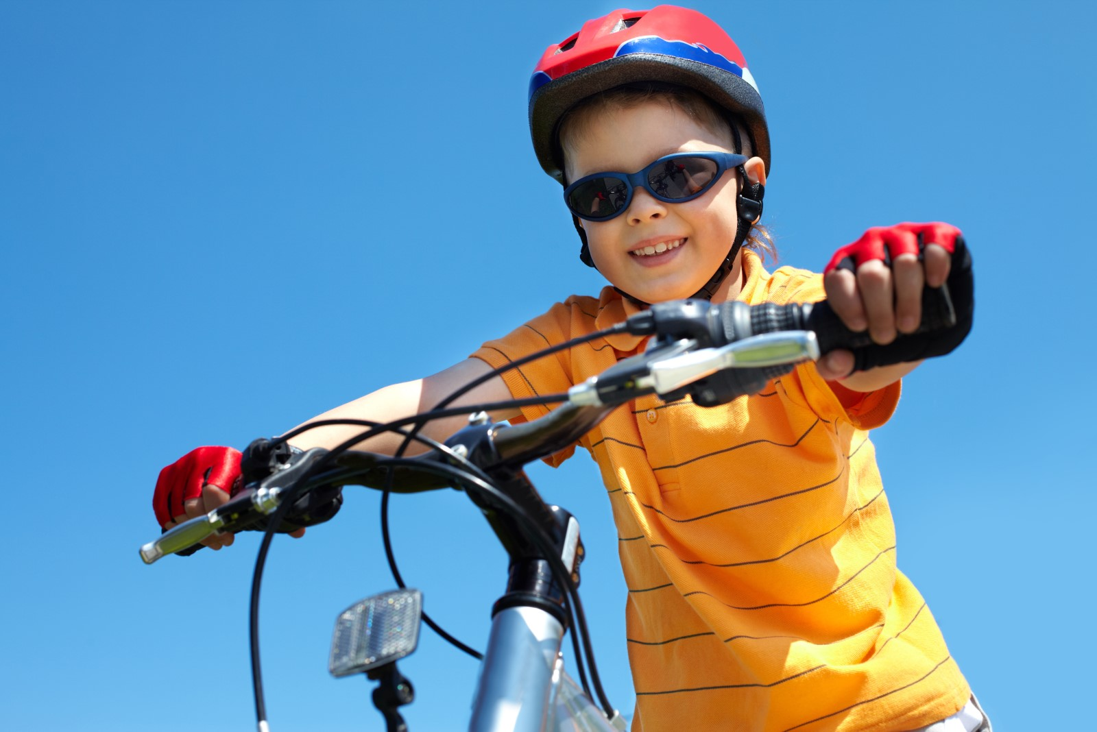 boy in red helmet holding bicycle handlebars