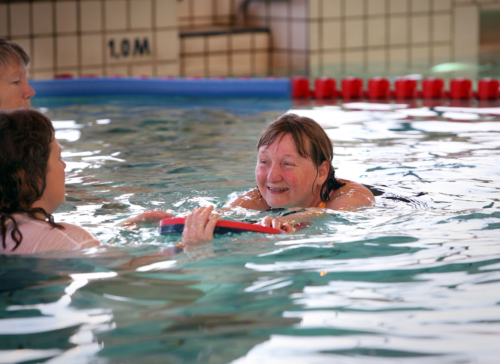 instructor teaching an adult woman how to swim
