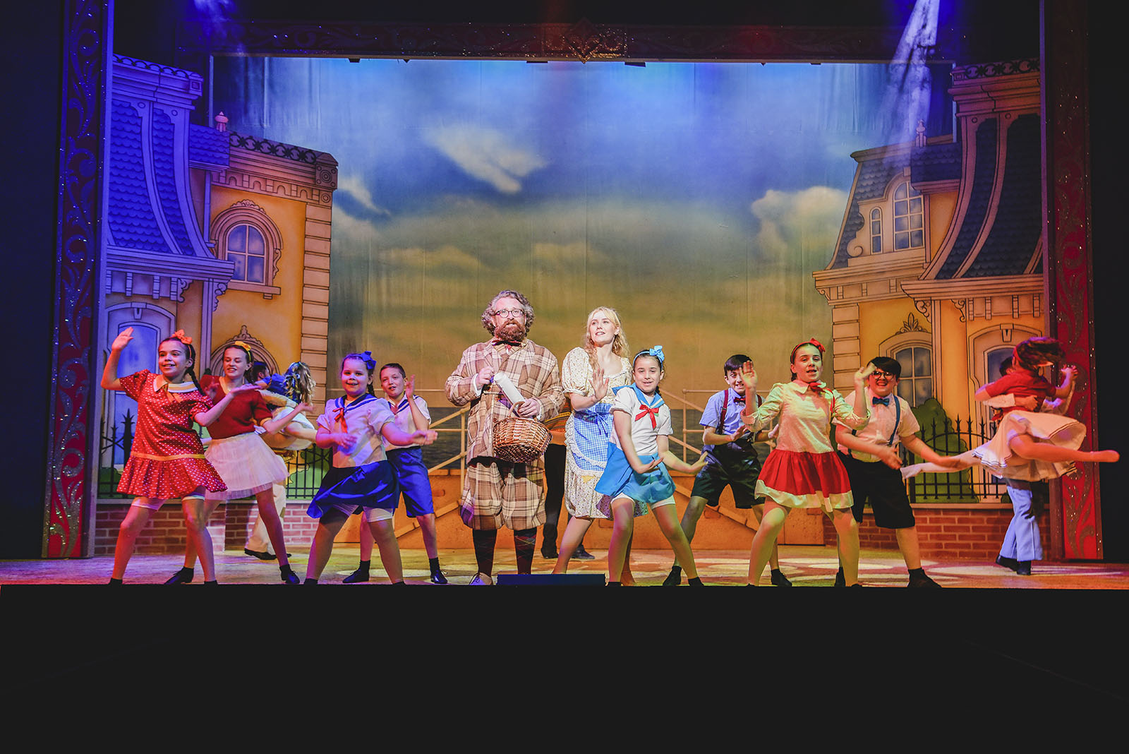 adults and children performing on a stage in cinderella panto