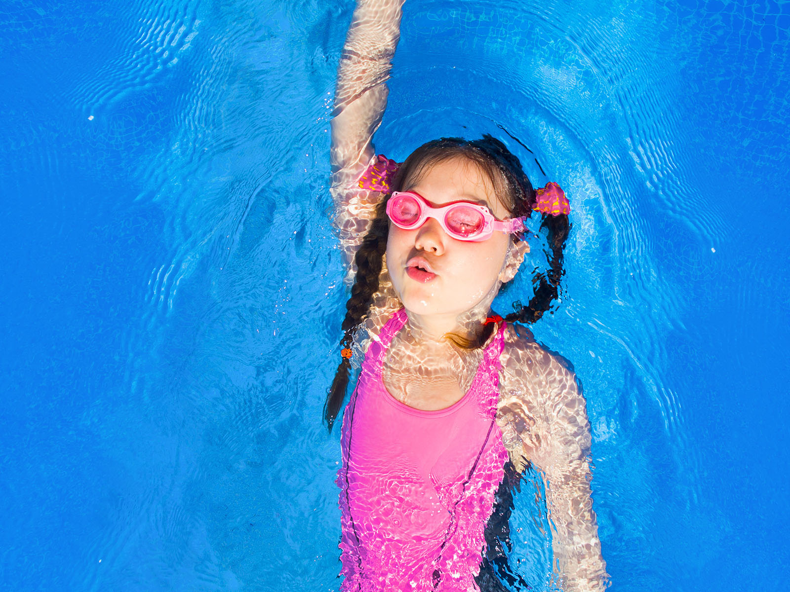 young girl swimming in a pink costume and goggles doing backstroke