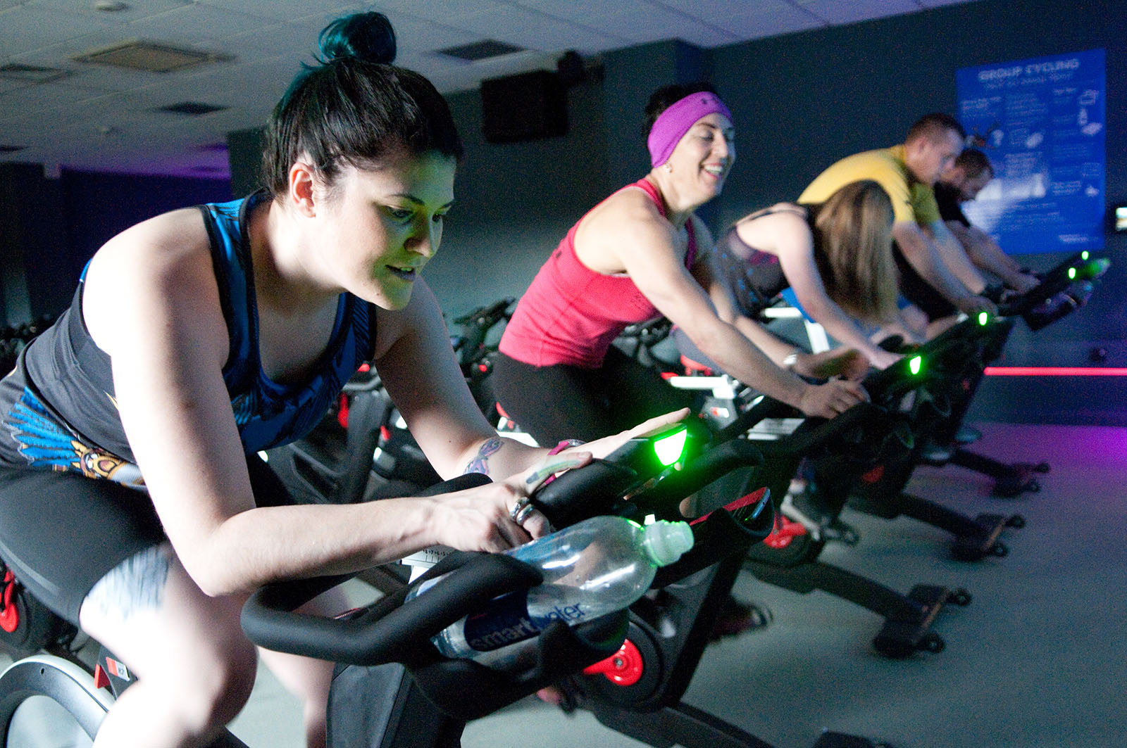 group of women riding on indoor cycling equipment
