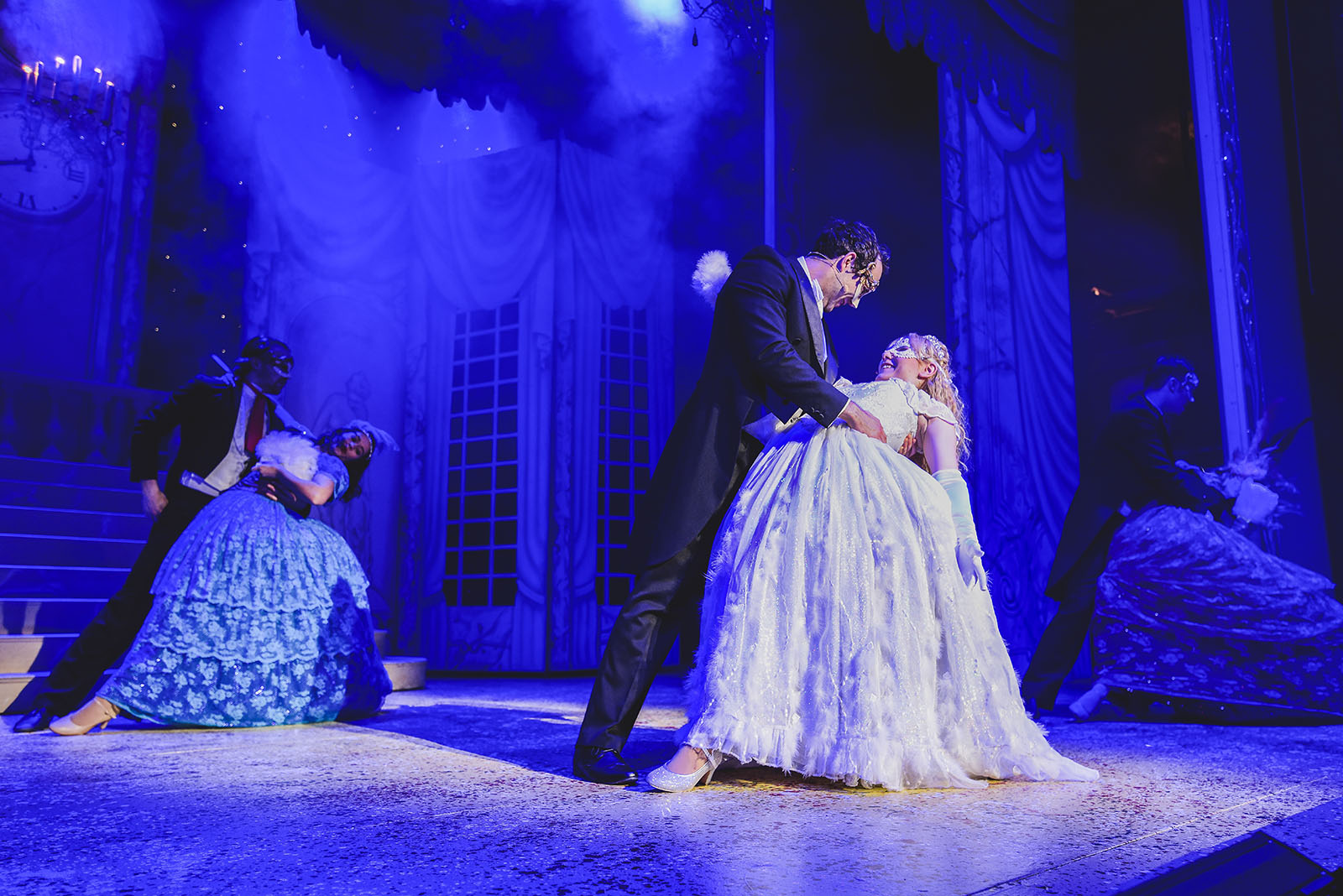 blue lit stage with prince charming and cinderella in panto performance