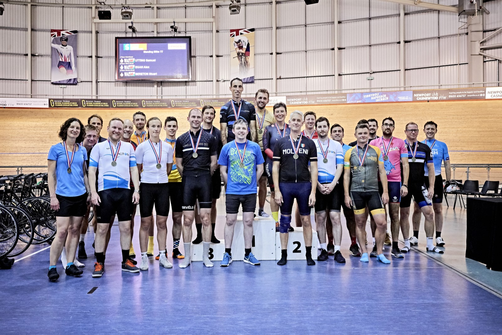 Group of people in cycling kit wearing medals