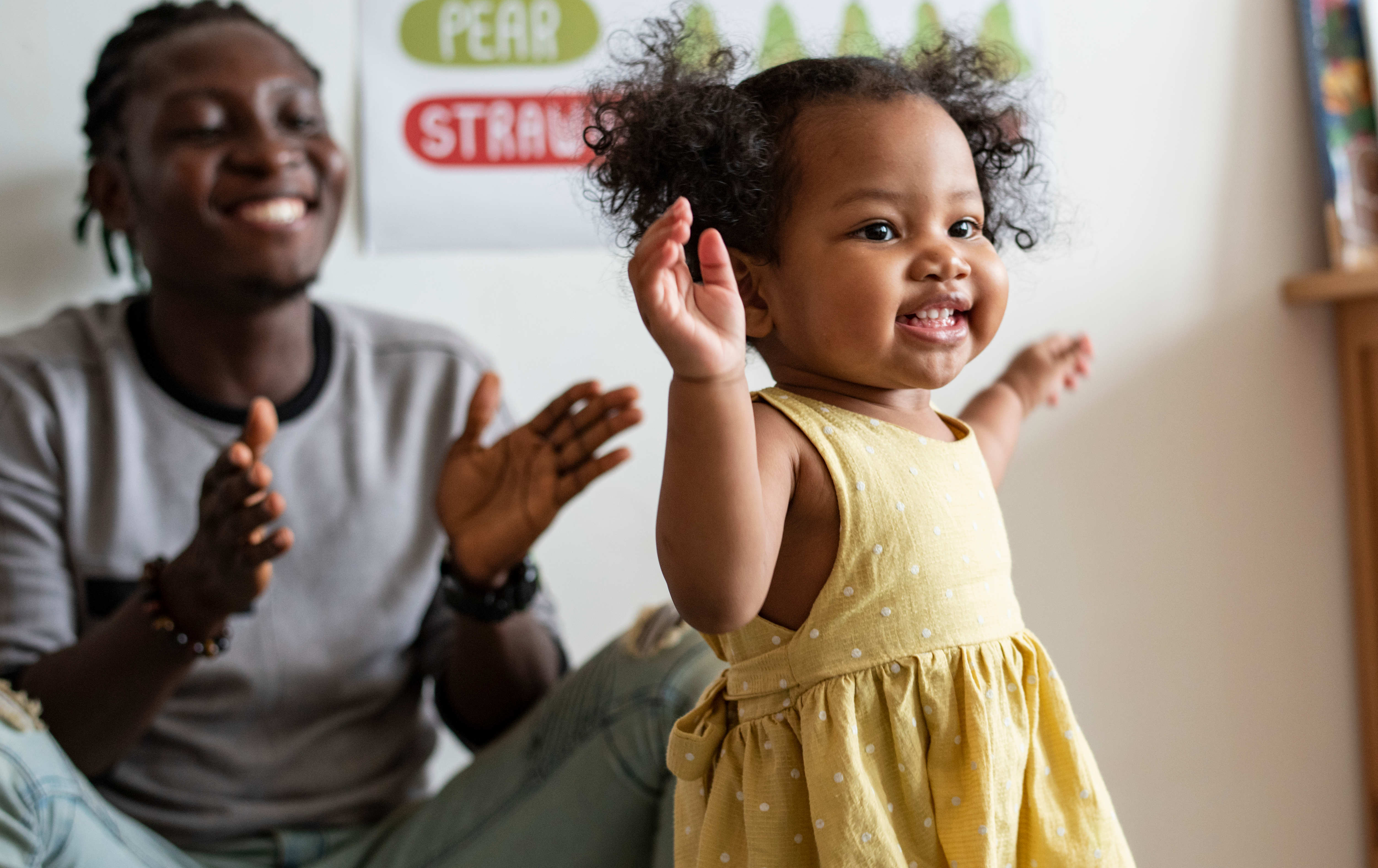 Little girl in yellow dress dances as father watches on clapping