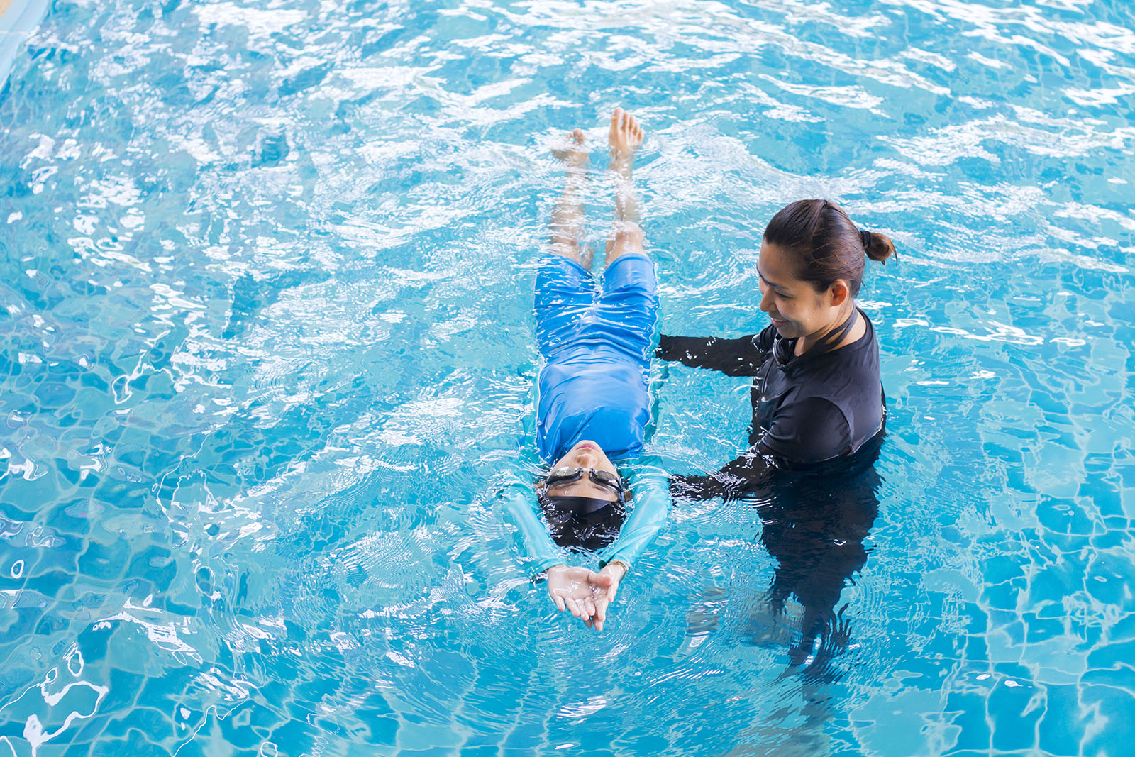 swimming instructor showing a young boy how to float