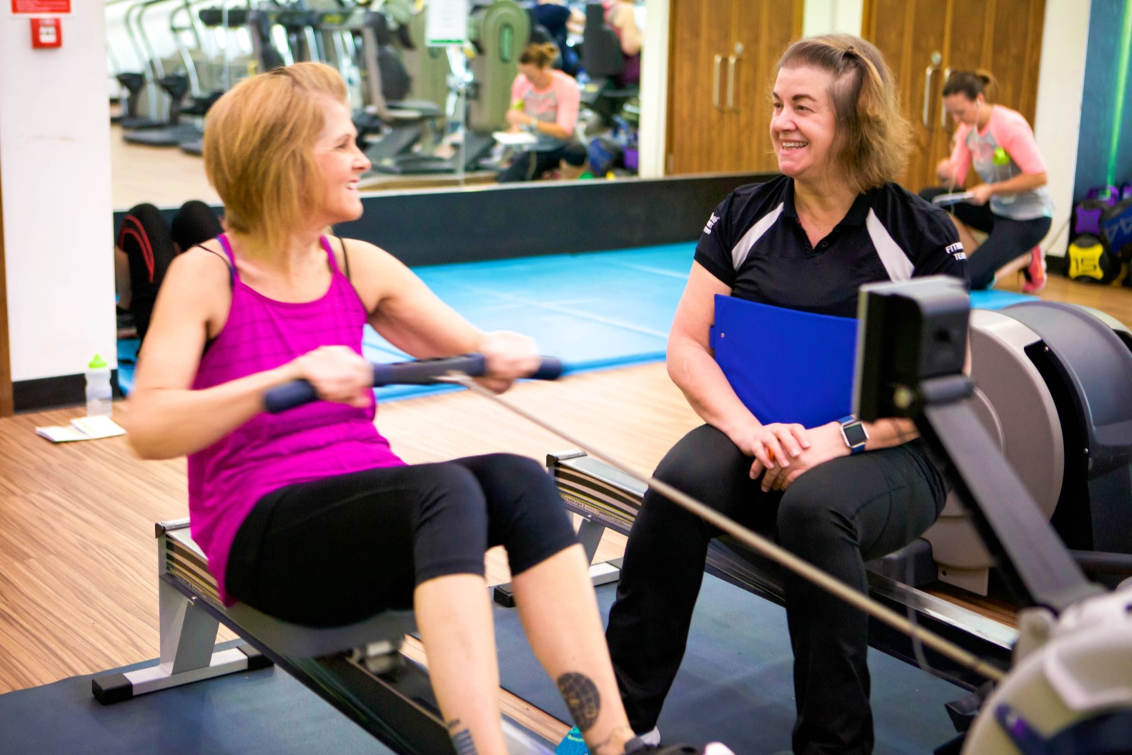 instructor supporting person on rowing machine.jpg