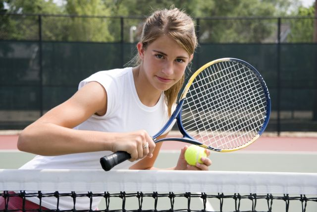 Teenage girl in white top holding yellow and black raquet