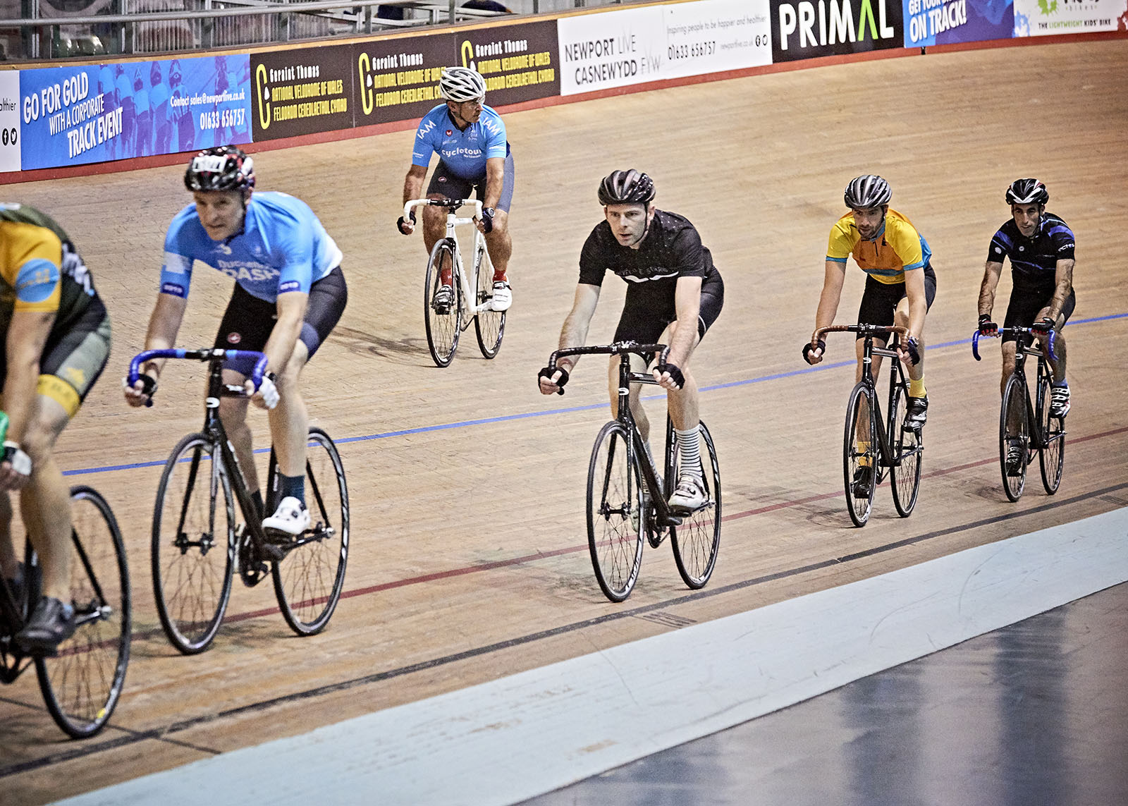 mix of people track cycling on an indoor track